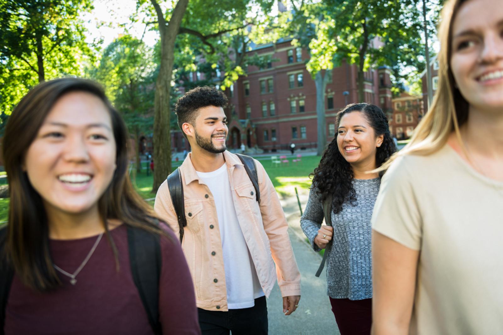 Students walking around campus, smiling