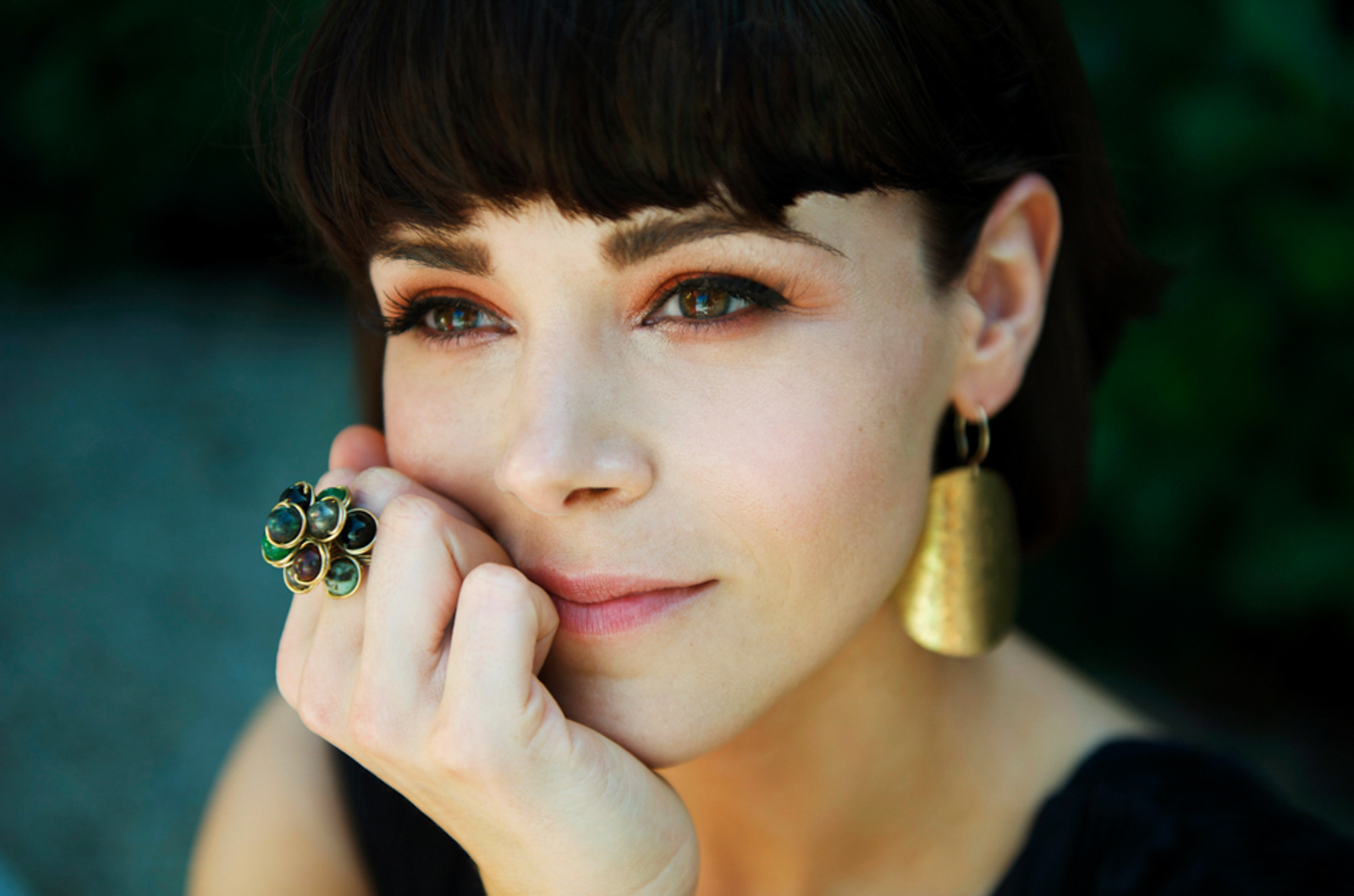 Portrait of woman with earrings and flower ring, looking pensive