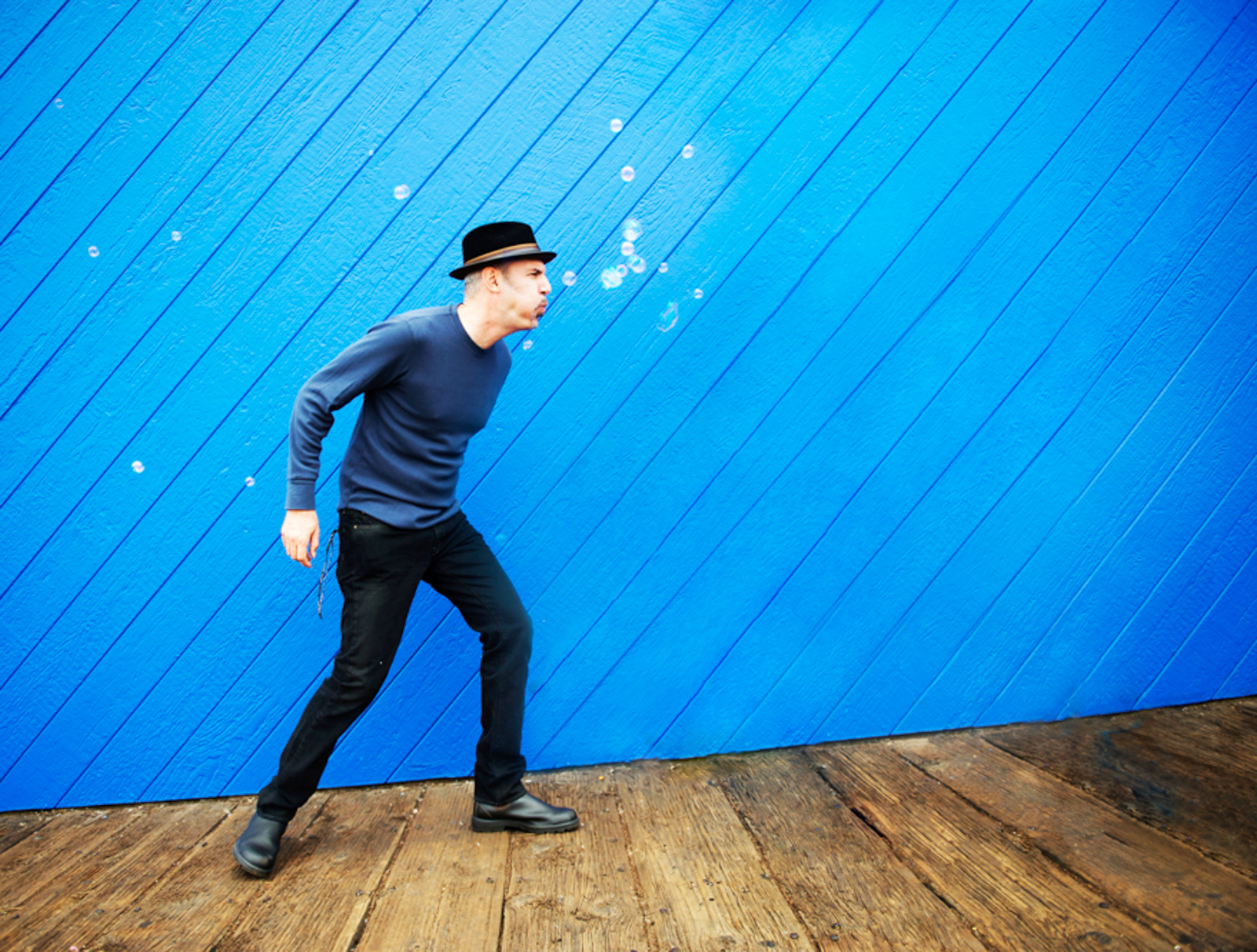 Portrait of musician blowing bubbles in front of bright blue background