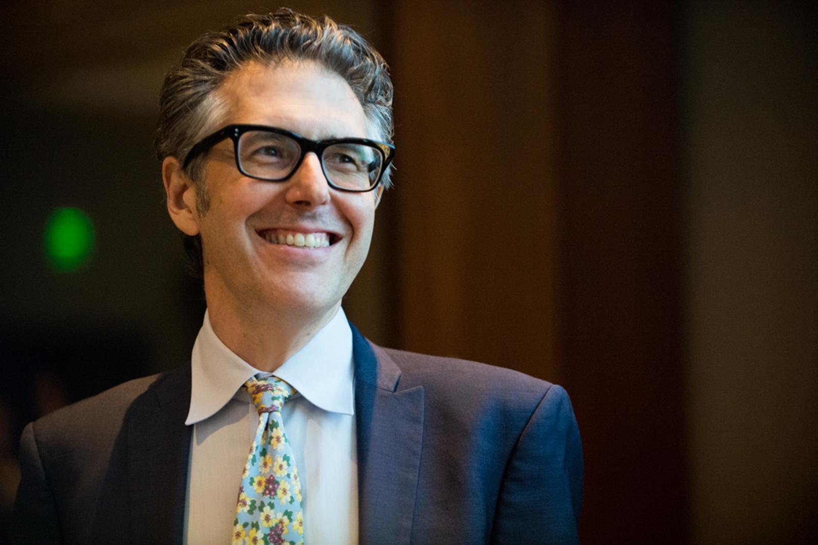 Portrait of radio host Ira Glass smiling, looking away
