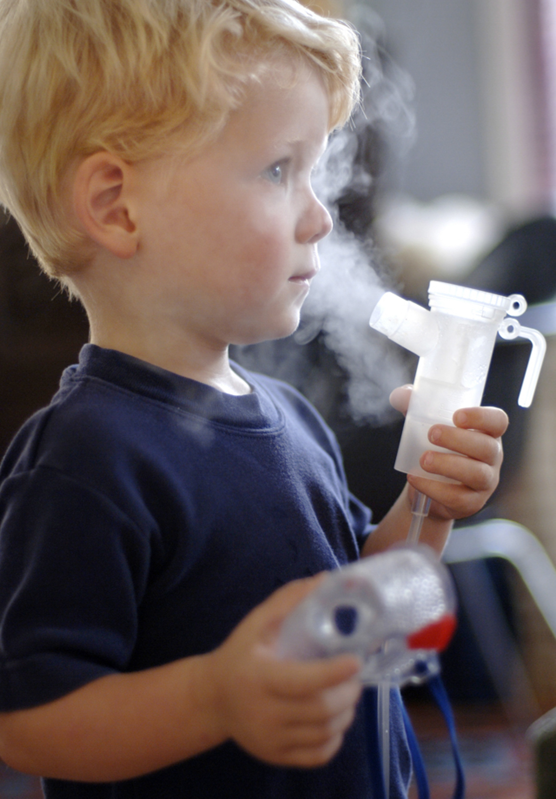 Child holding a breathing aid device