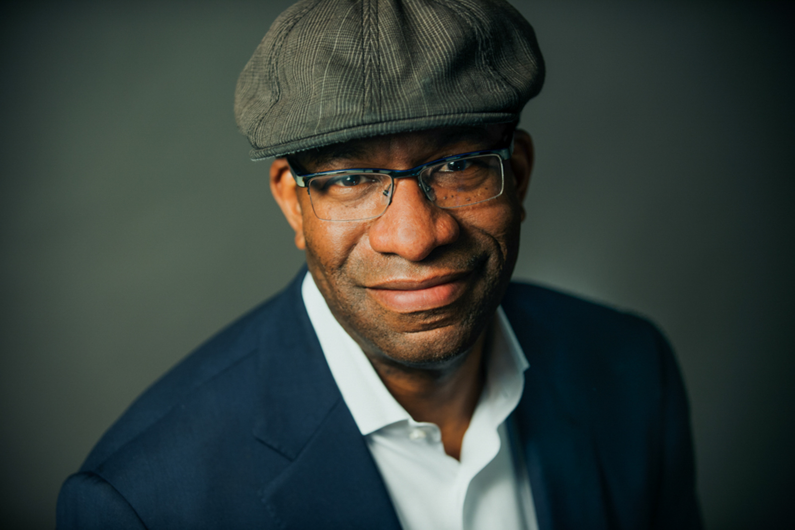 Portrait of a man wearing a hat and glasses, with a soft smile