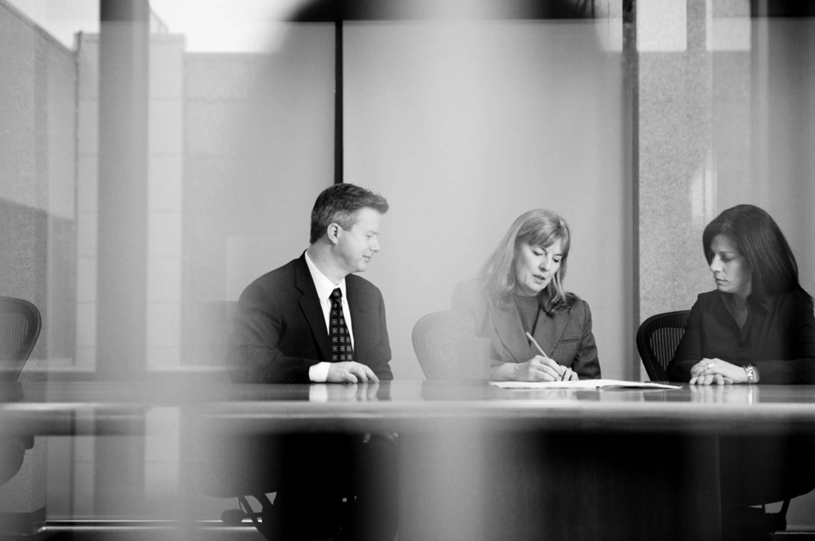 Two women and one man having a business meeting, seen through a glass door