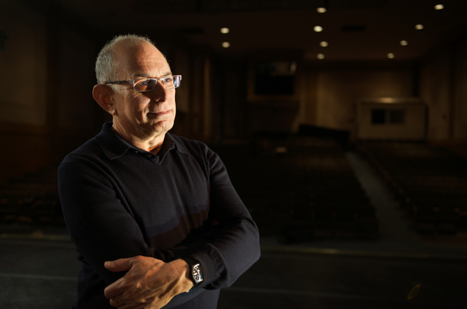 Environmental portrait of man with arms crossed, in auditorium