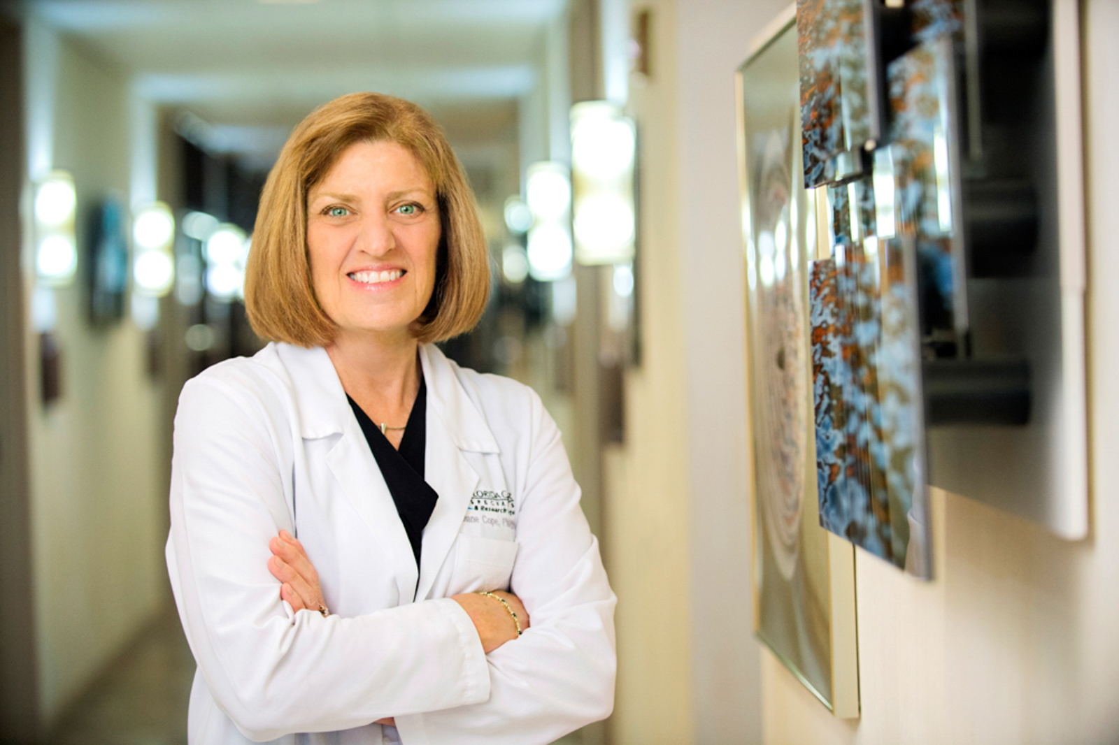 Portrait of health professional with her armed crossed, smiling in hallway