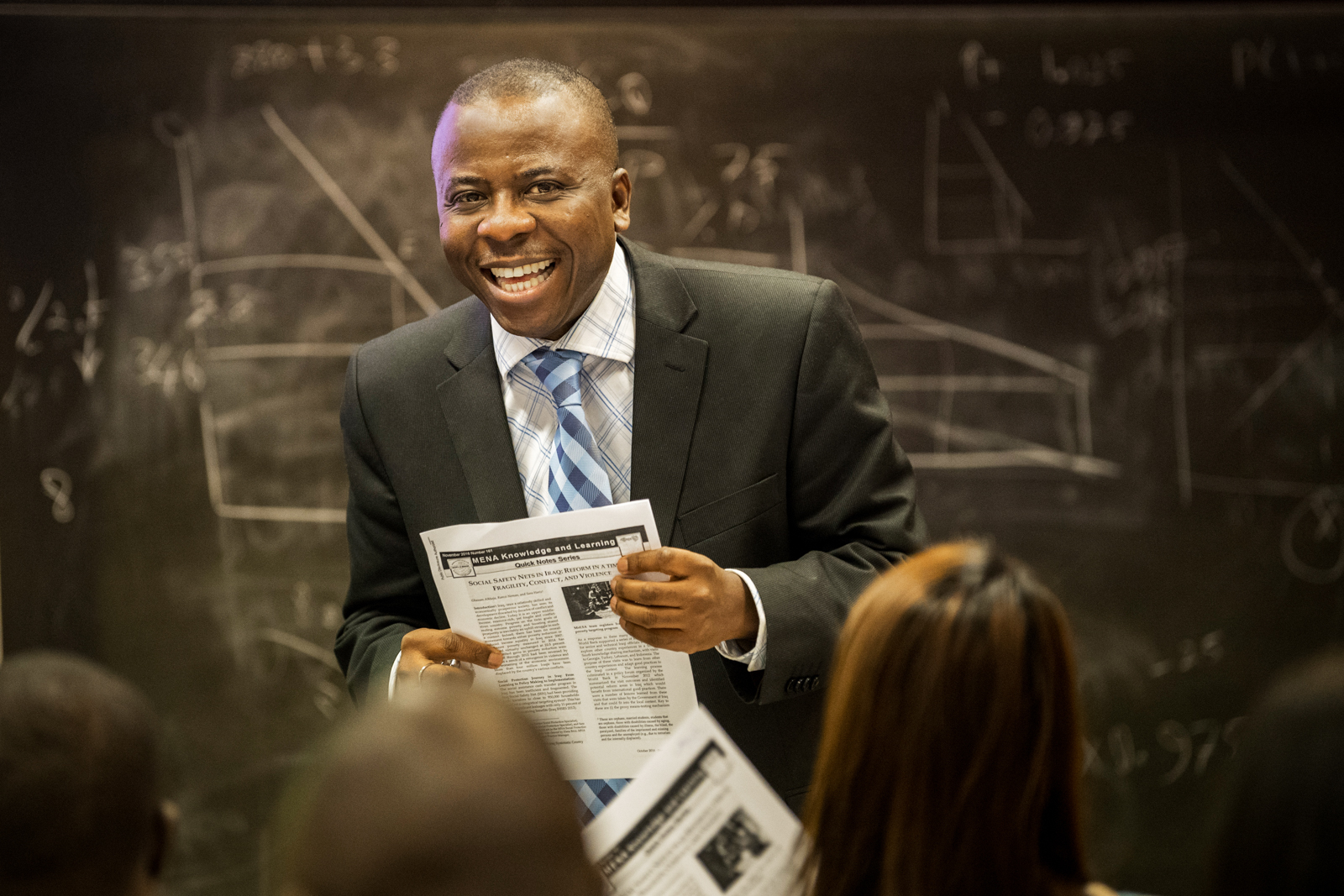 Instructor smiling in class, in front of blackboard