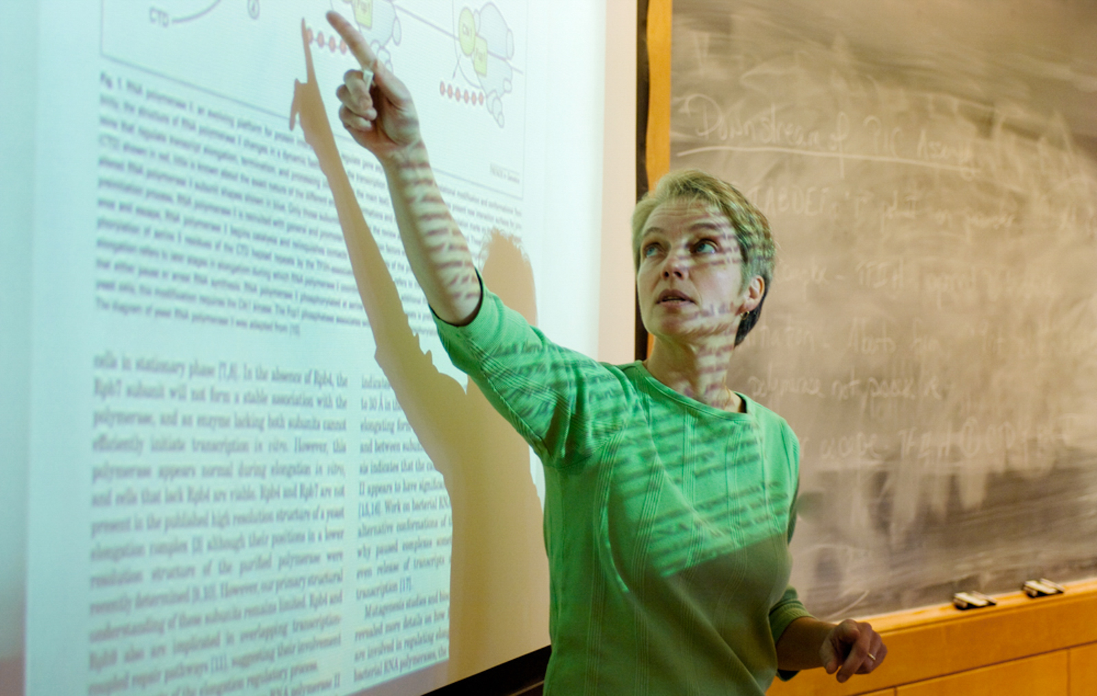 Instructor pointing at presentation on board, with reflections