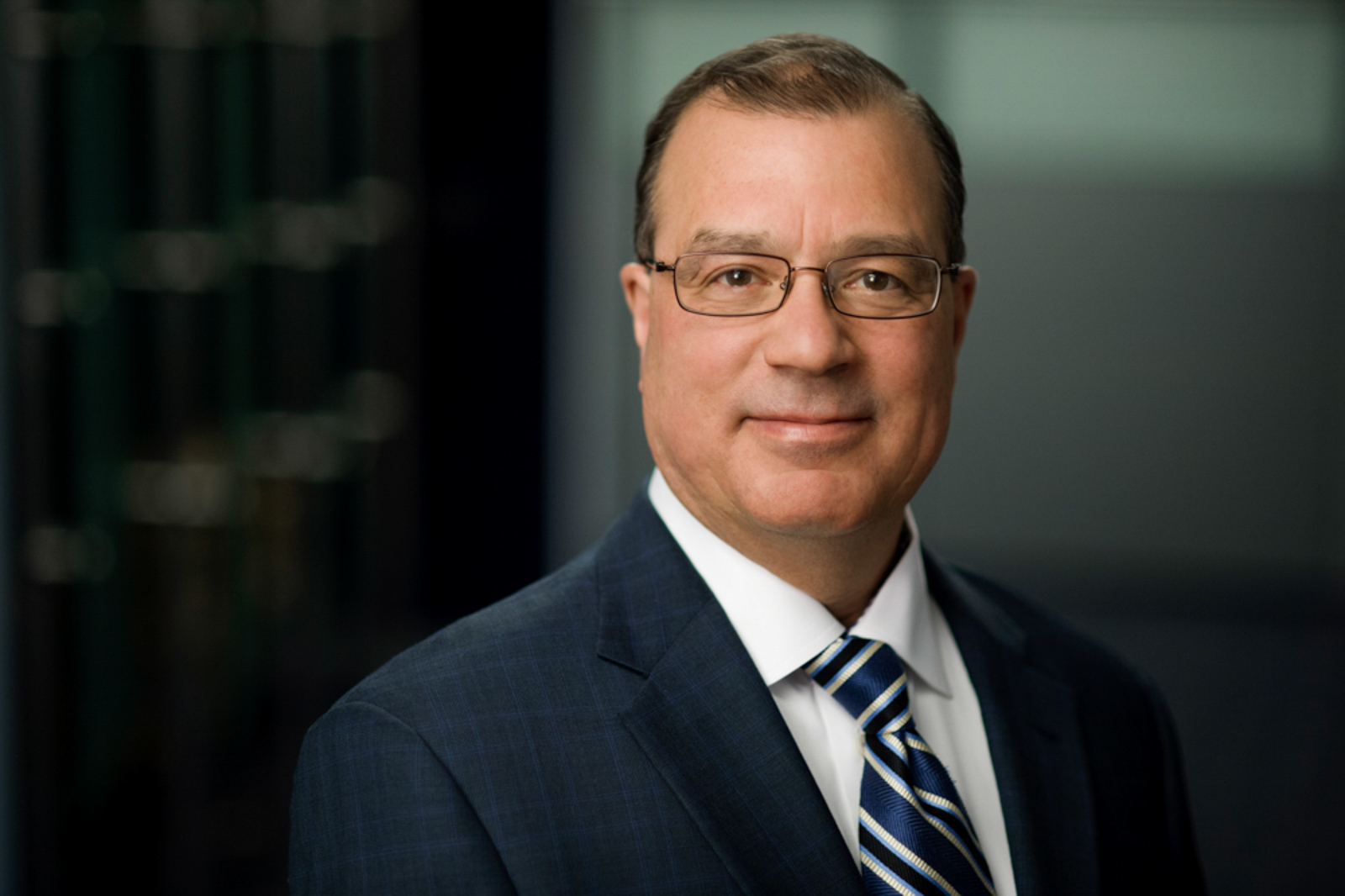 Portrait of business man wearing suit and glasses, with a soft smile