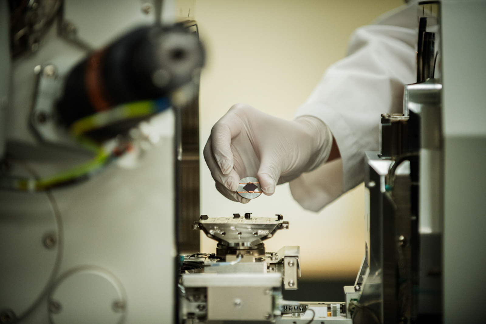 Detail shot of lab tech holding a small piece of machinery