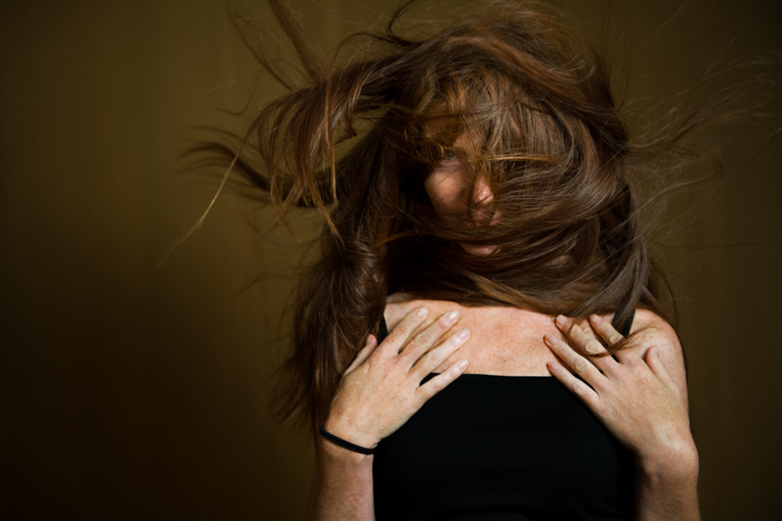 Portrait of woman with long messy hair covering her face