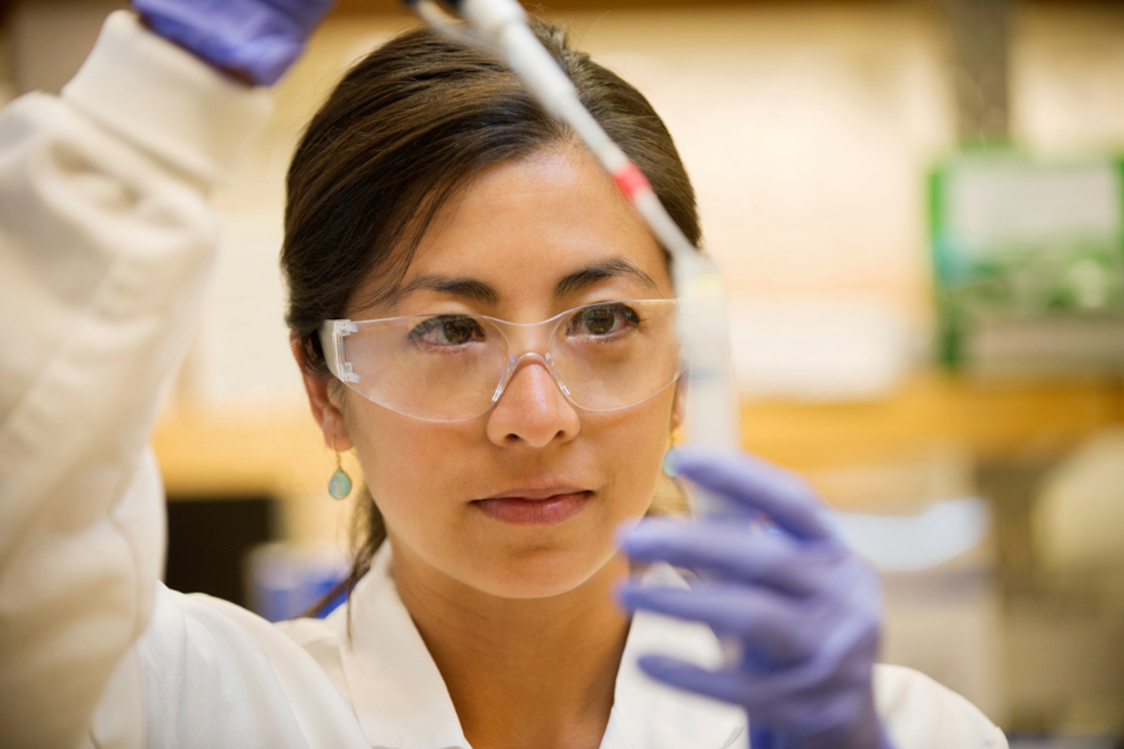 Female lab tech working on test tube, wearing goggles