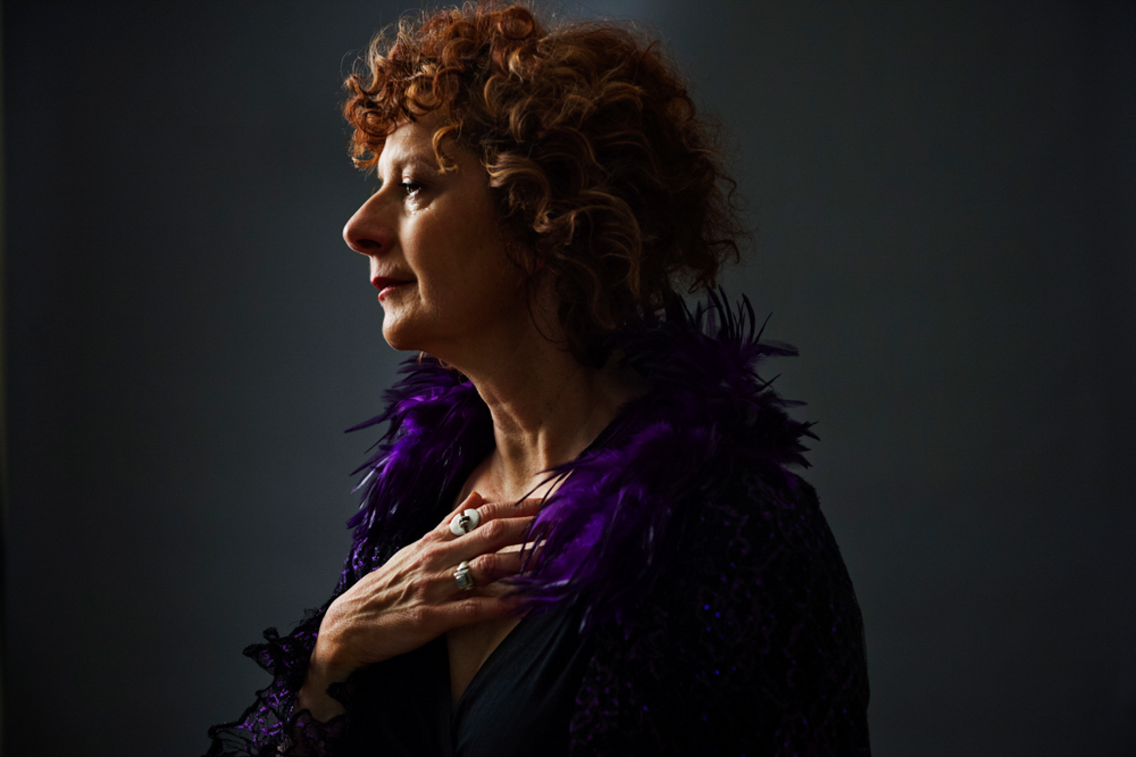 Portrait of woman with red hair and purple coat, looking pensive
