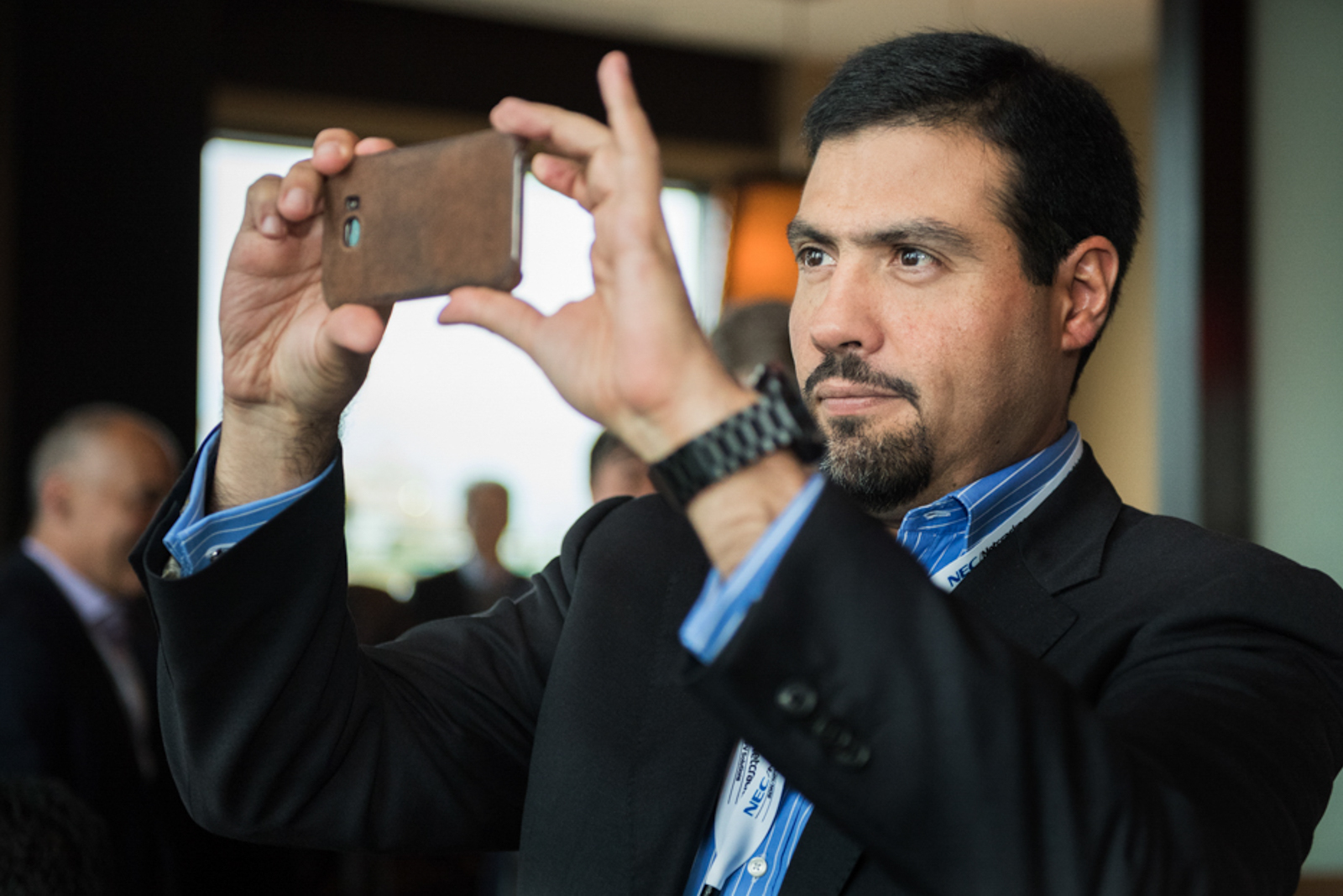 Candid image of man in a business gathering, taking a cellphone photo