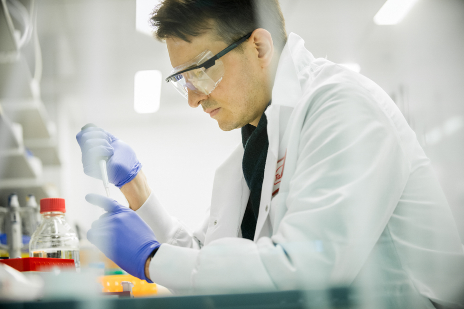 Lab technician working on test tubes, wearing protective gloves and goggles