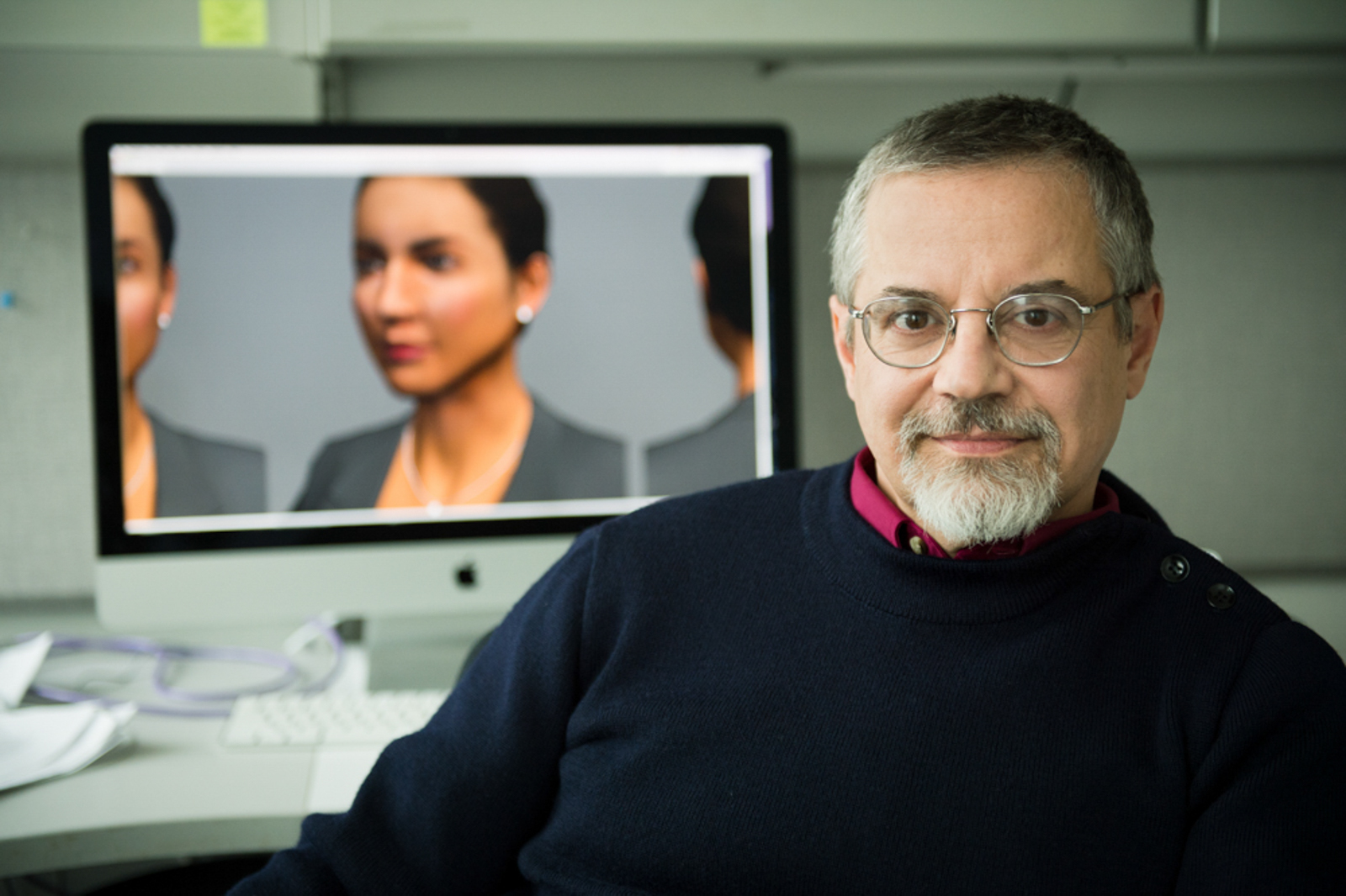 Portrait of professor with his work shown in a computer in the background
