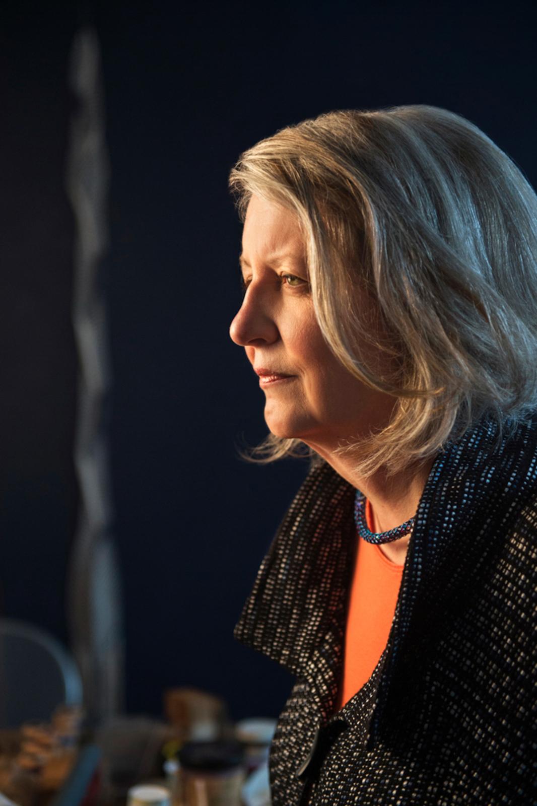 Side profile of older woman in a studio, looking pensive