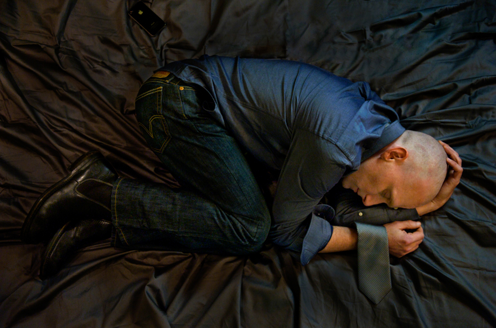 Overhead portrait of man lying in bed, with eyes closed