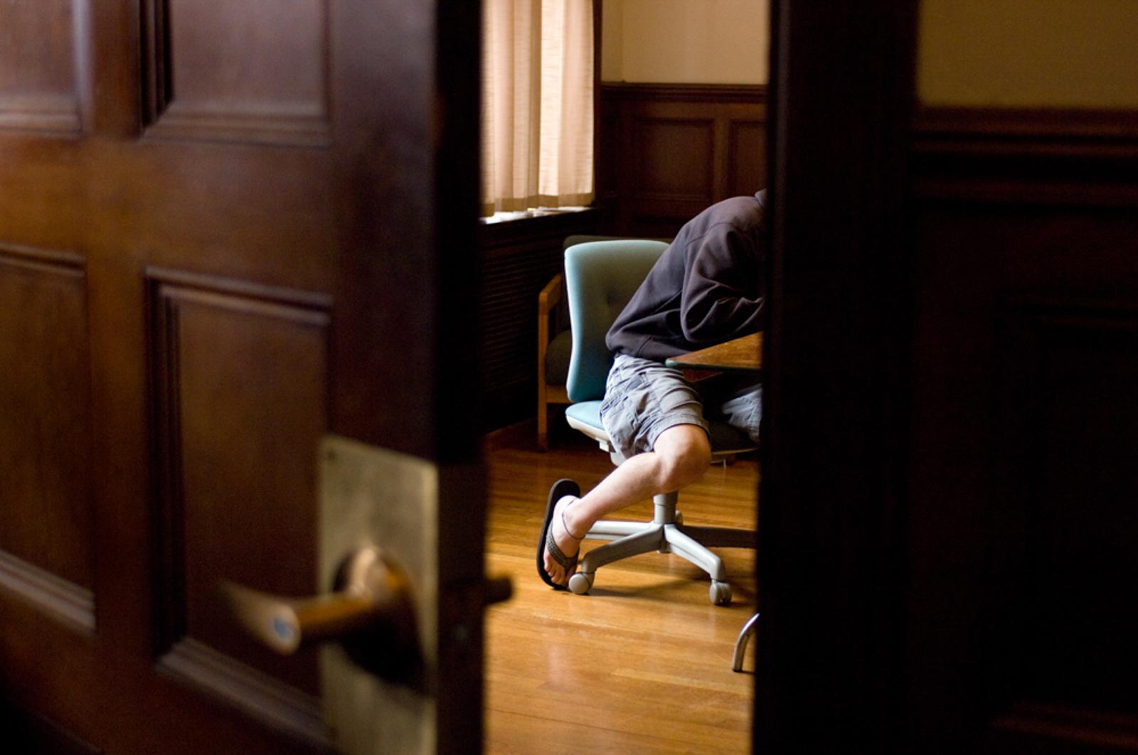 Student working in room seen through an open door, wearing flip flops