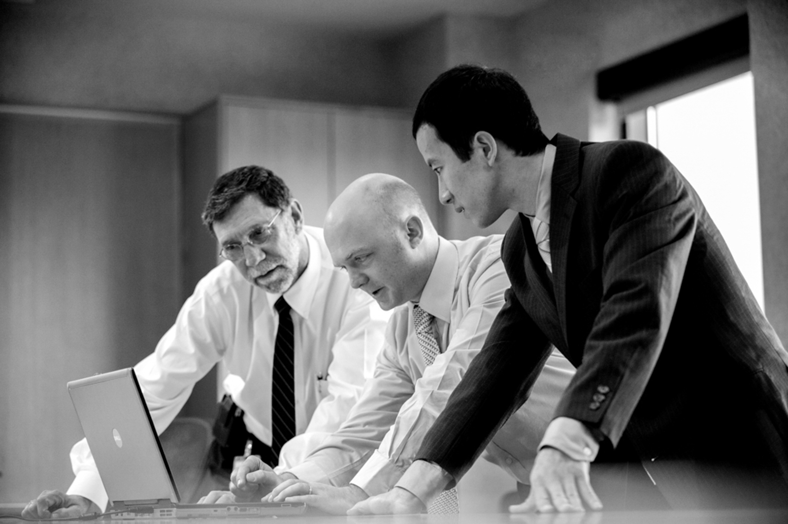 Candid of three men looking at laptop, in office