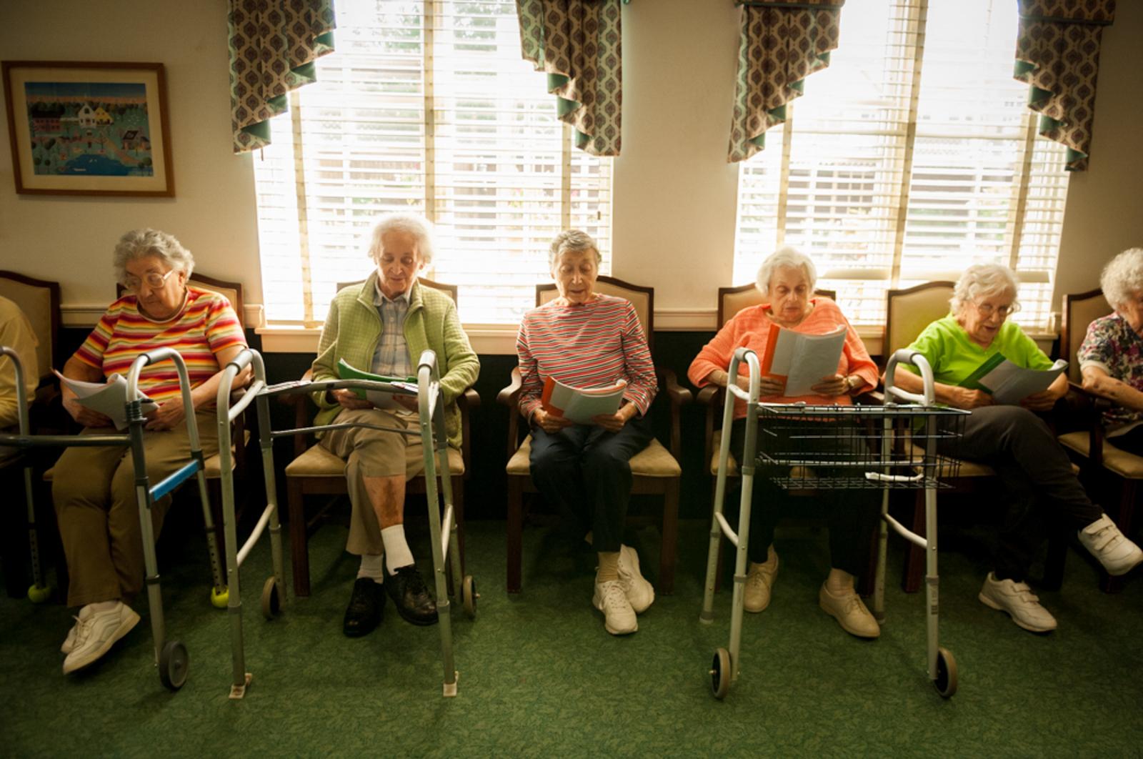 Group of elderly women sitting in cozy room, reading