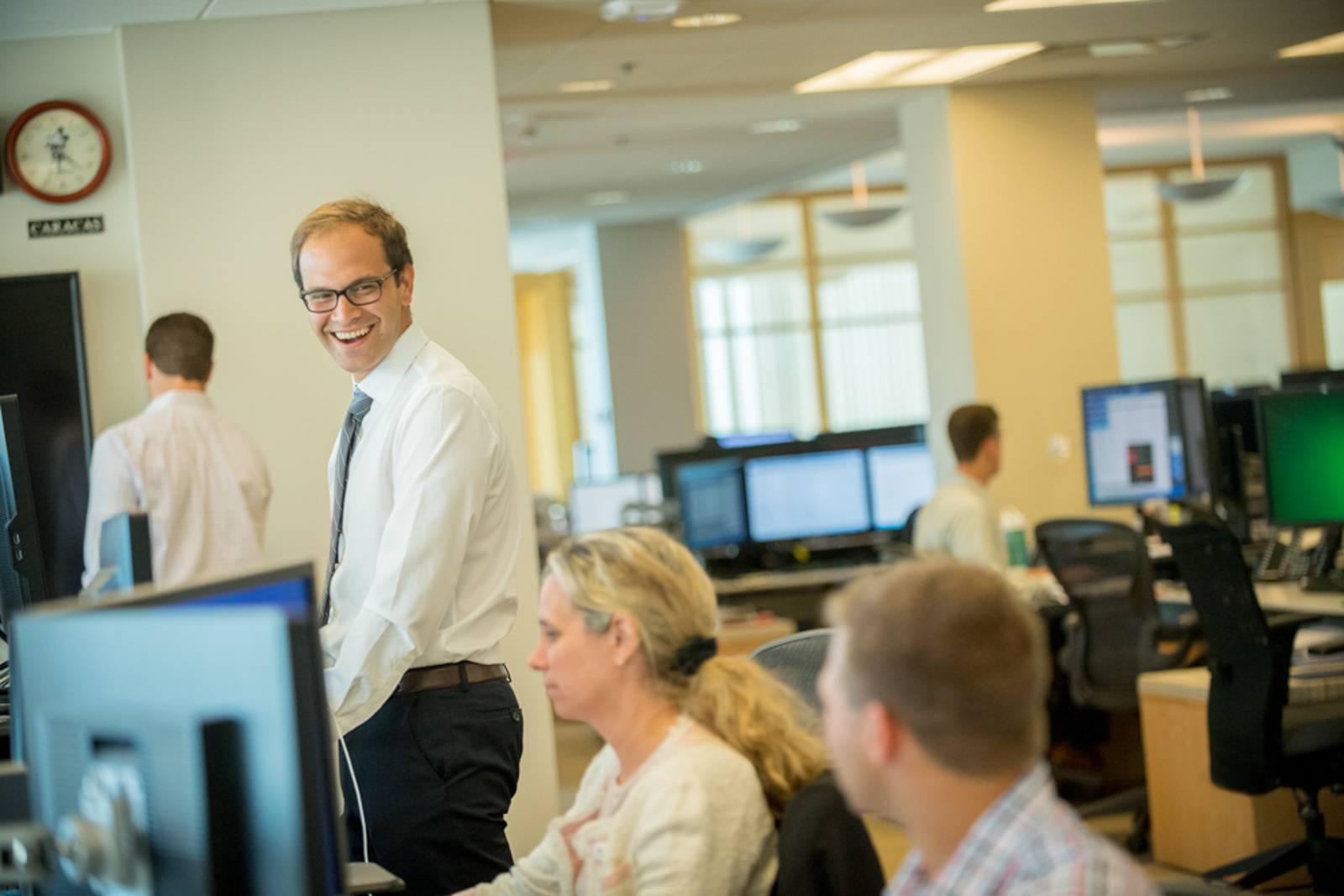 Candid office culture scene, two people sit in the foreground, a man stands smiling in focus
