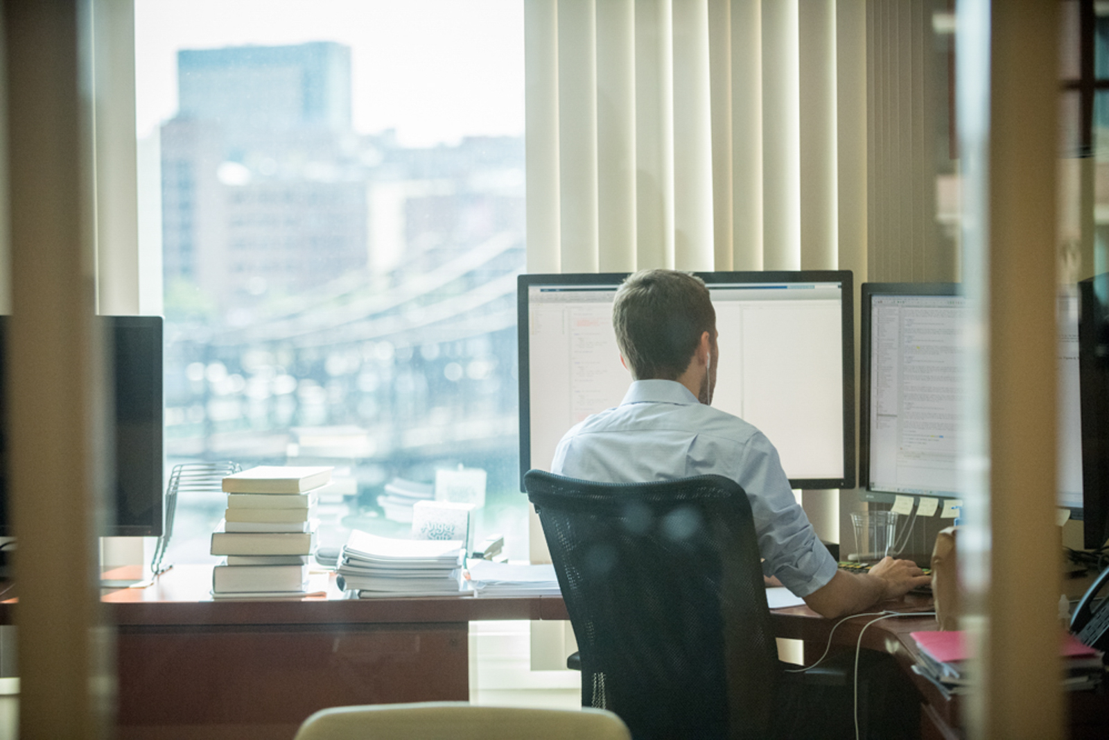 Environmental image of man sitting in front of a computer, with back facing the camera
