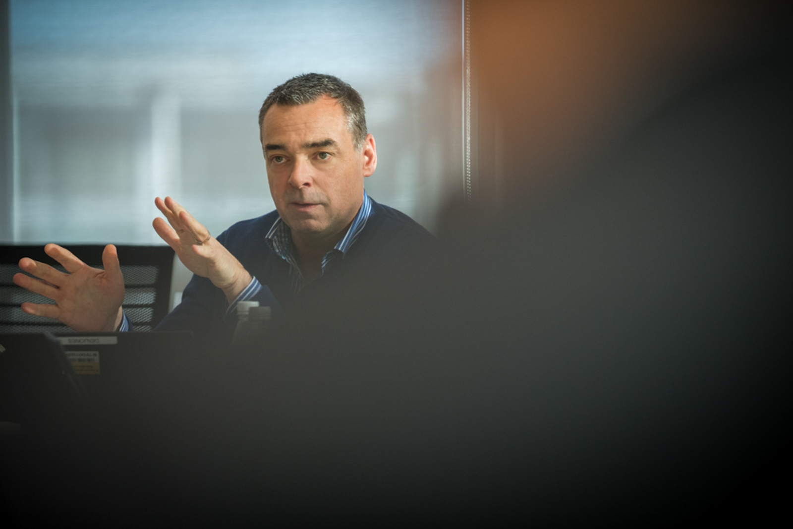 Partially covered business man, gesturing during meeting