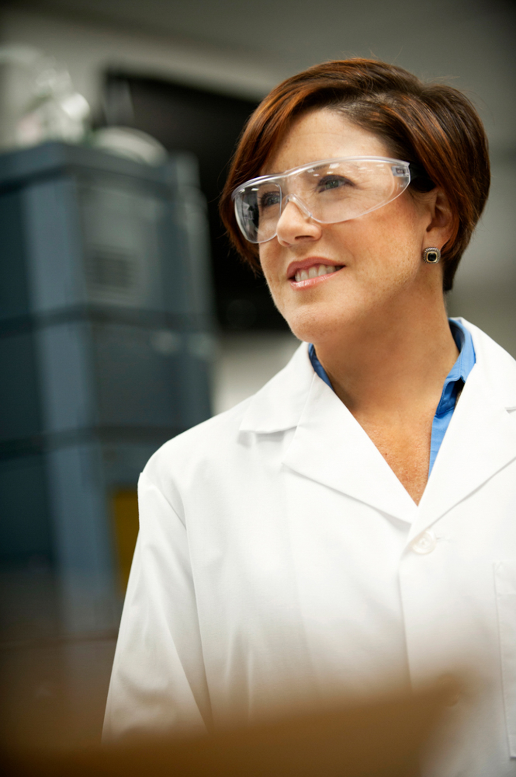 Female health professional wearing goggles, smiling and looking away