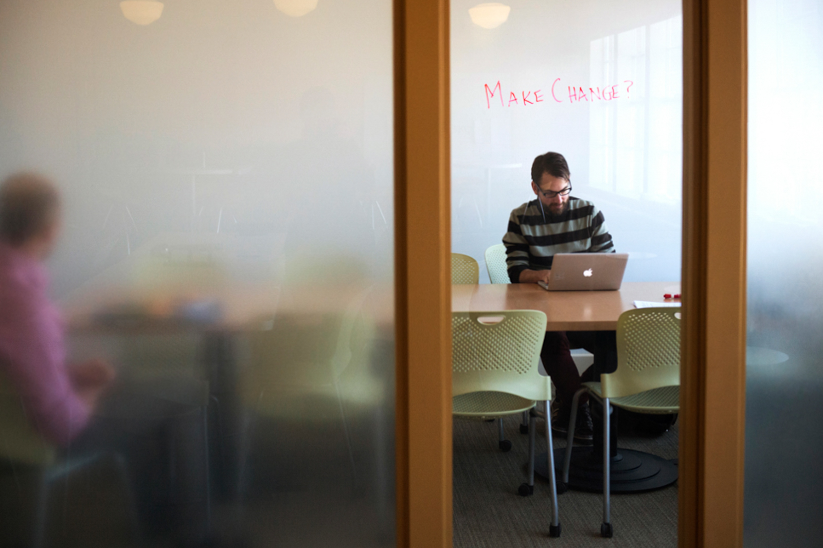Student sitting inside room, working on a laptop