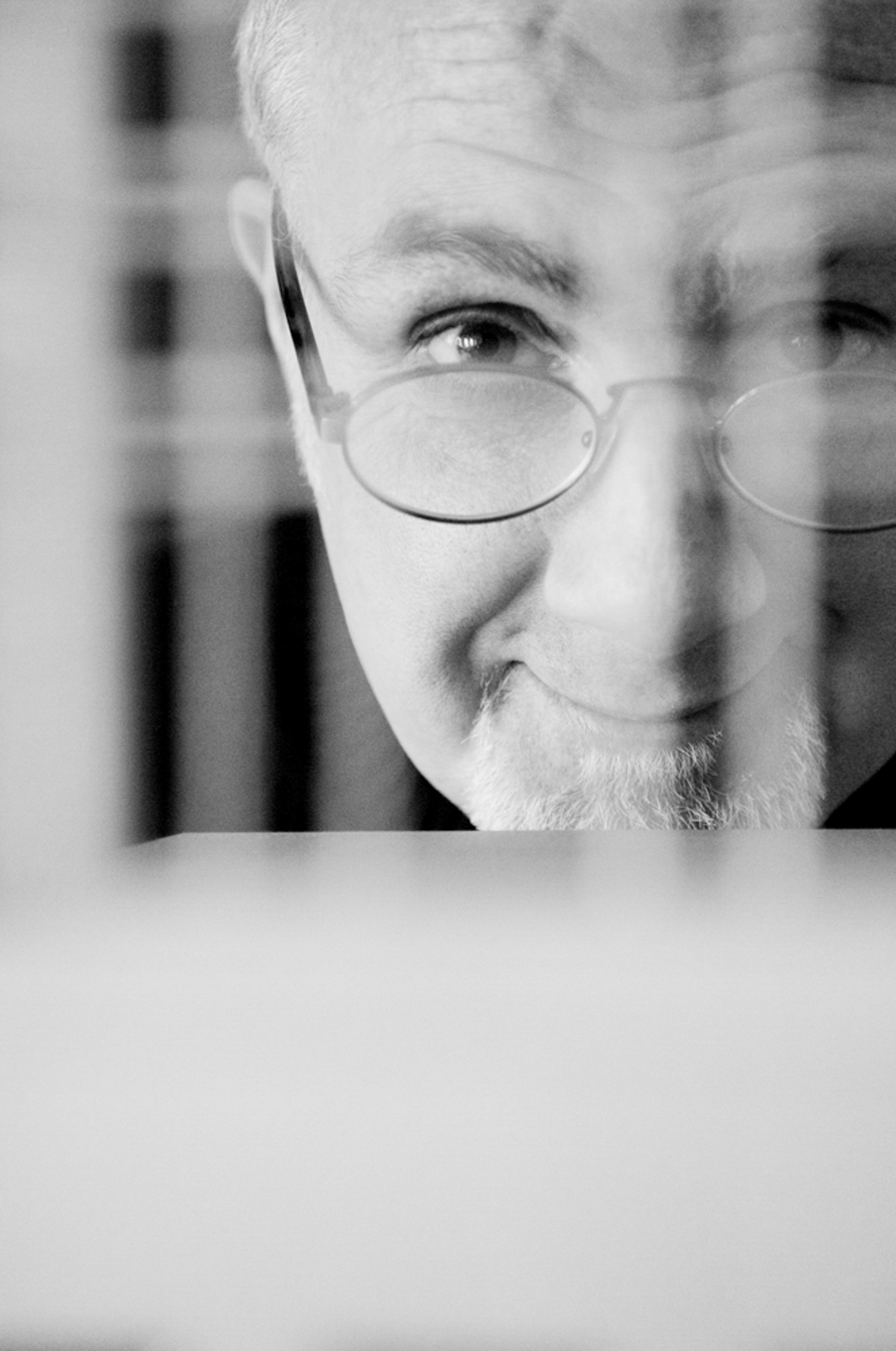 Close up of man wearing glasses, looking through a patterned element