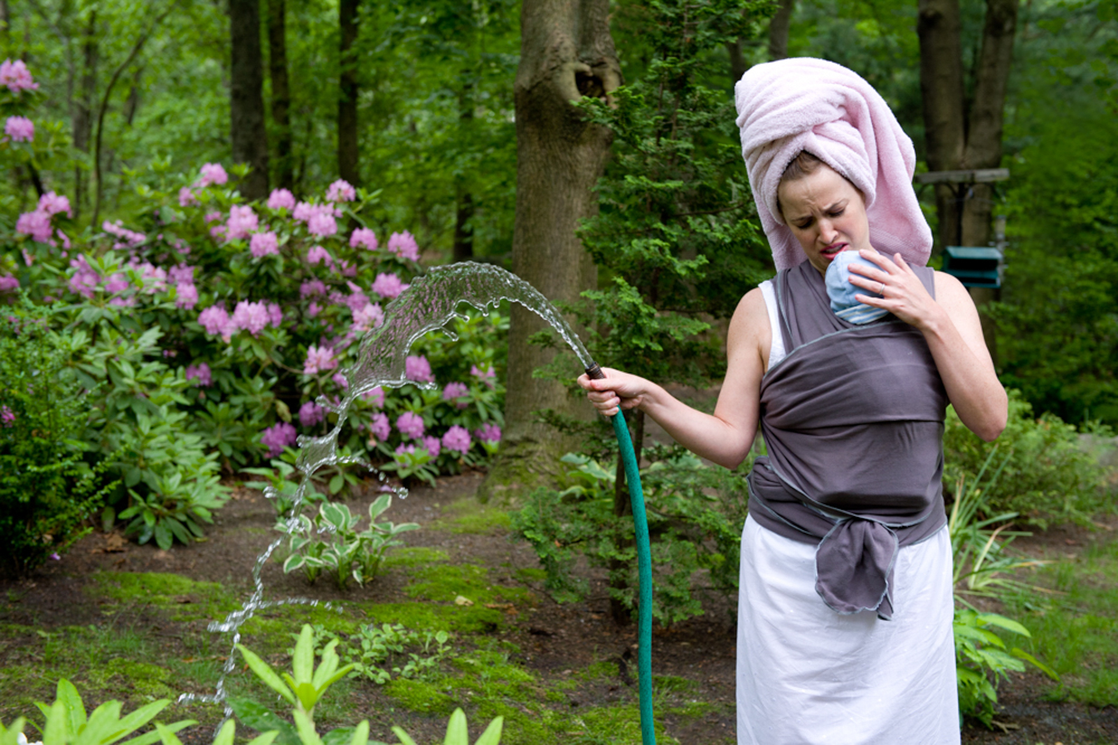 mother with child in wrap watering garden