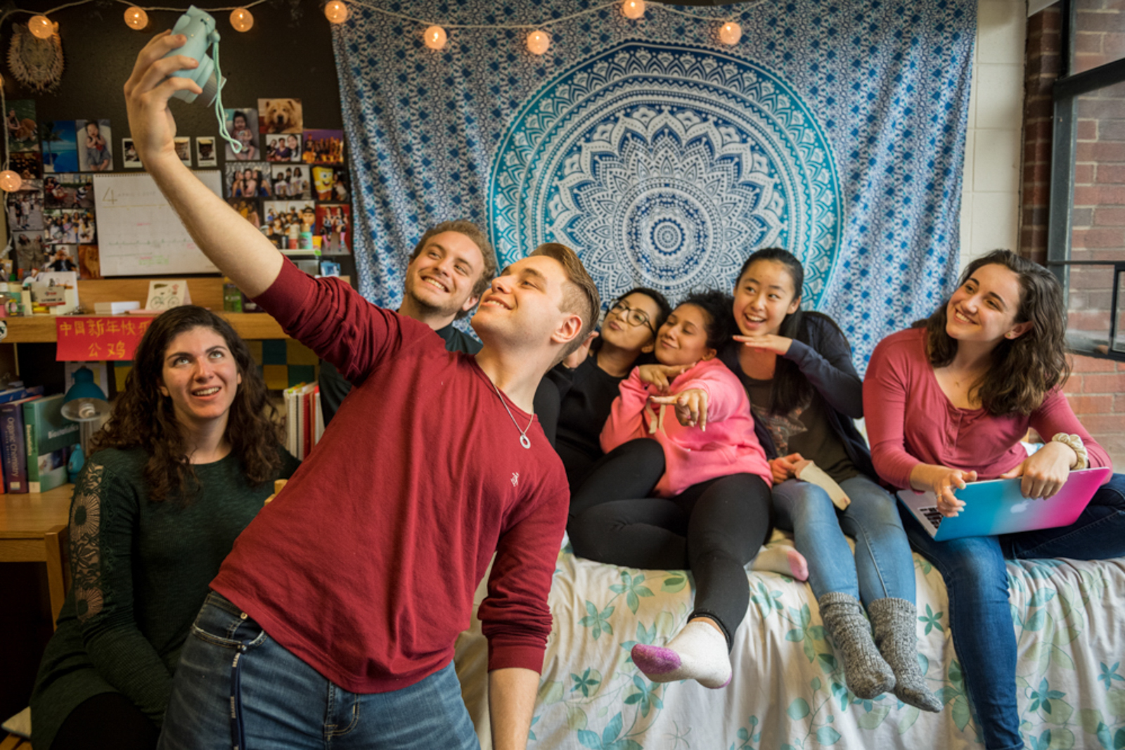 Group of students hanging out in dorm room, taking a fun selfie with an instant camera