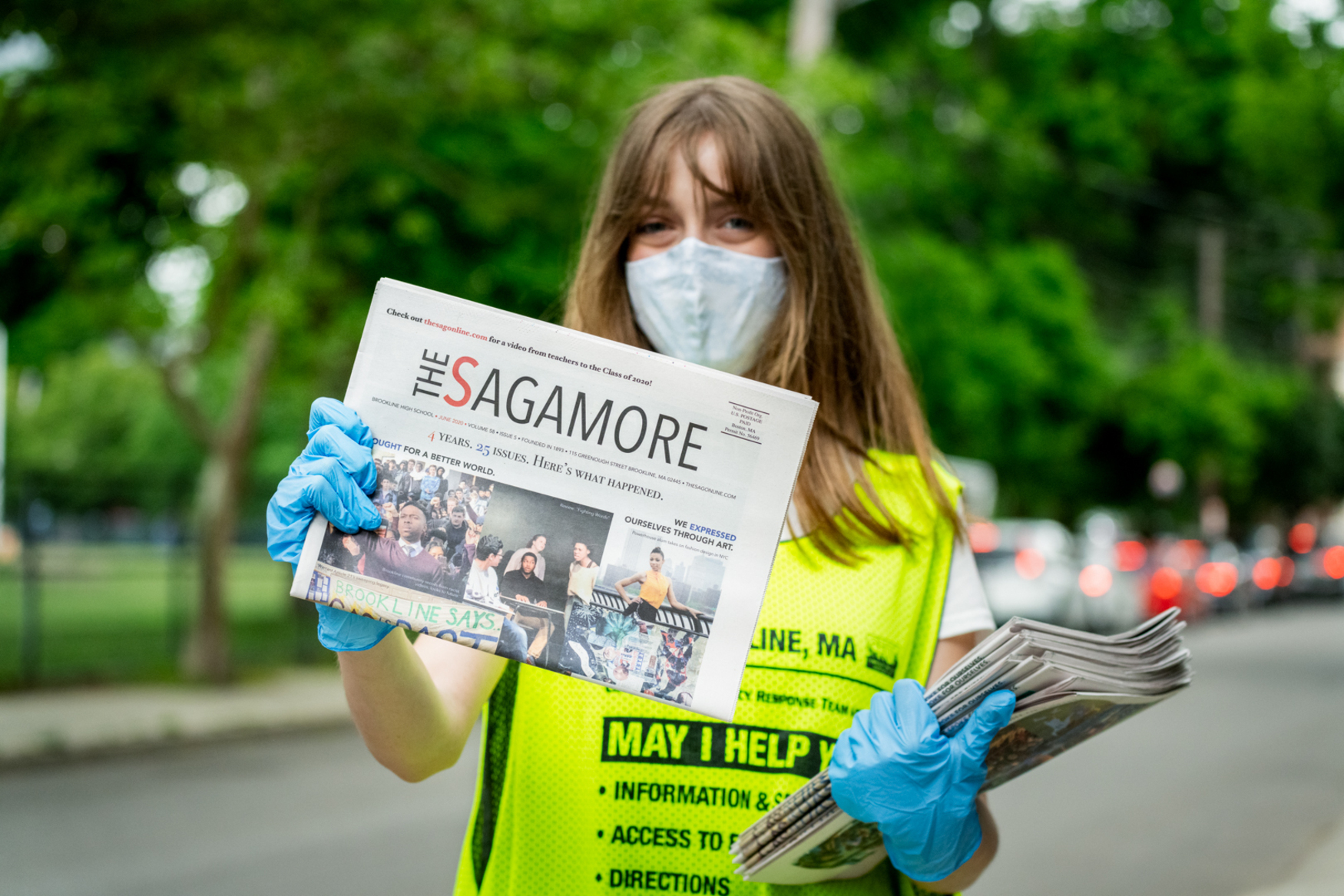 tween holding newspaper in gloves and mask