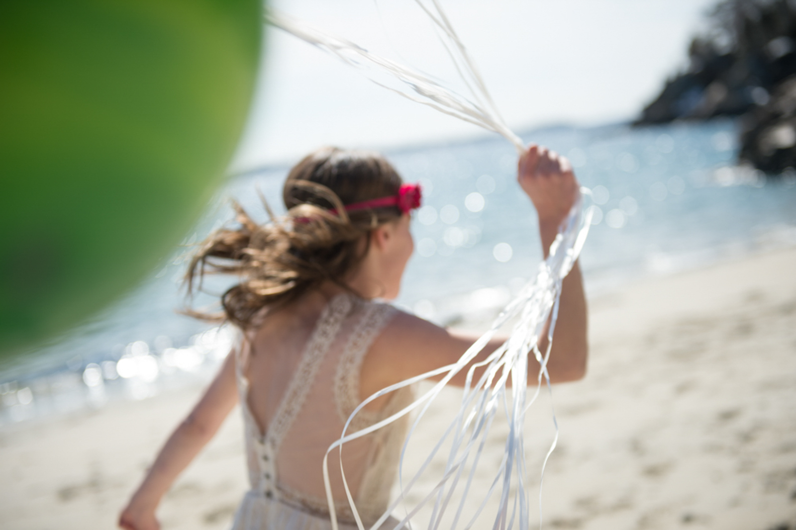 Portrait of child running at the beach, holding balloons