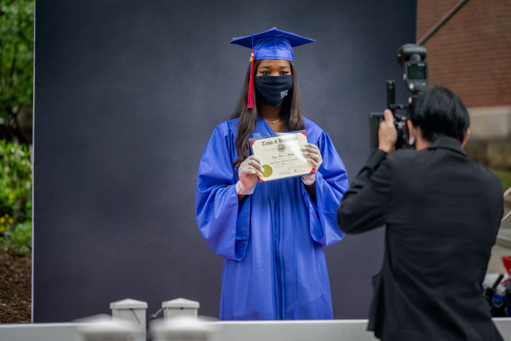 high school graduate in mask being photographed outside