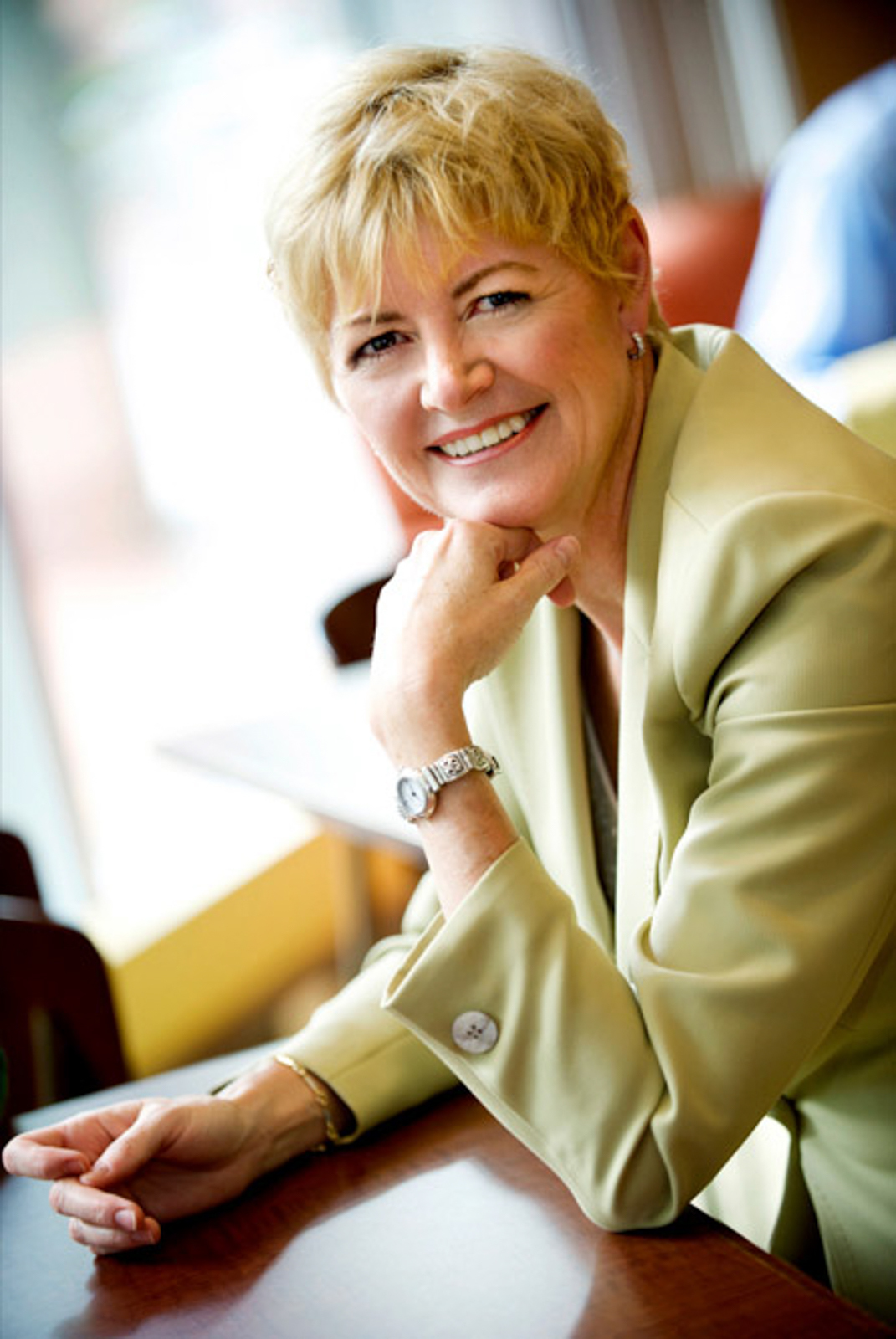 Portrait of business woman smiling, leaning on a desk