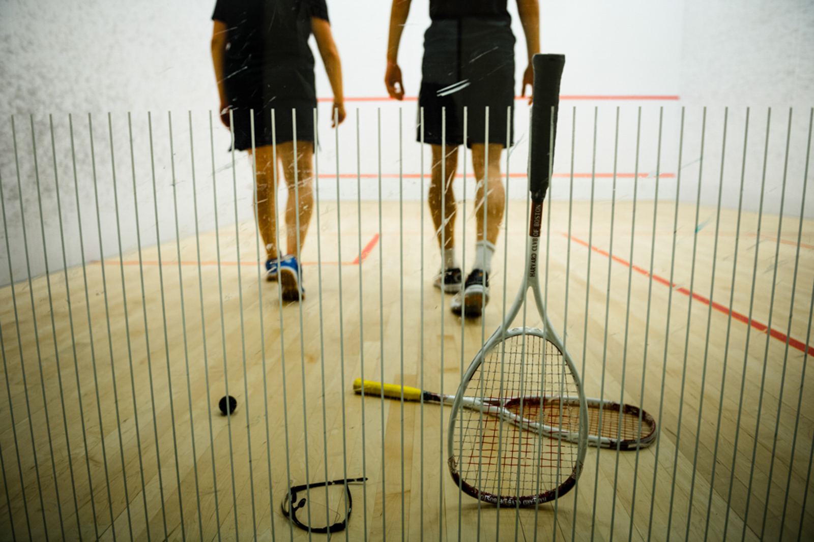 Two men playing tennis indoors, seen through glass