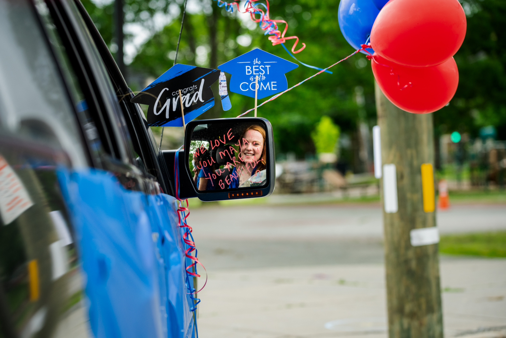 high school graduate in side view mirror with balloons