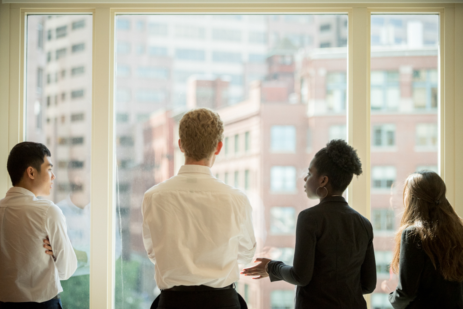Image of four young people in a business setting, looking outside a window