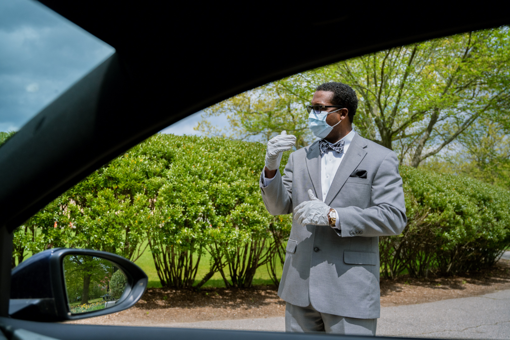 man in suit mask and gloves through car window