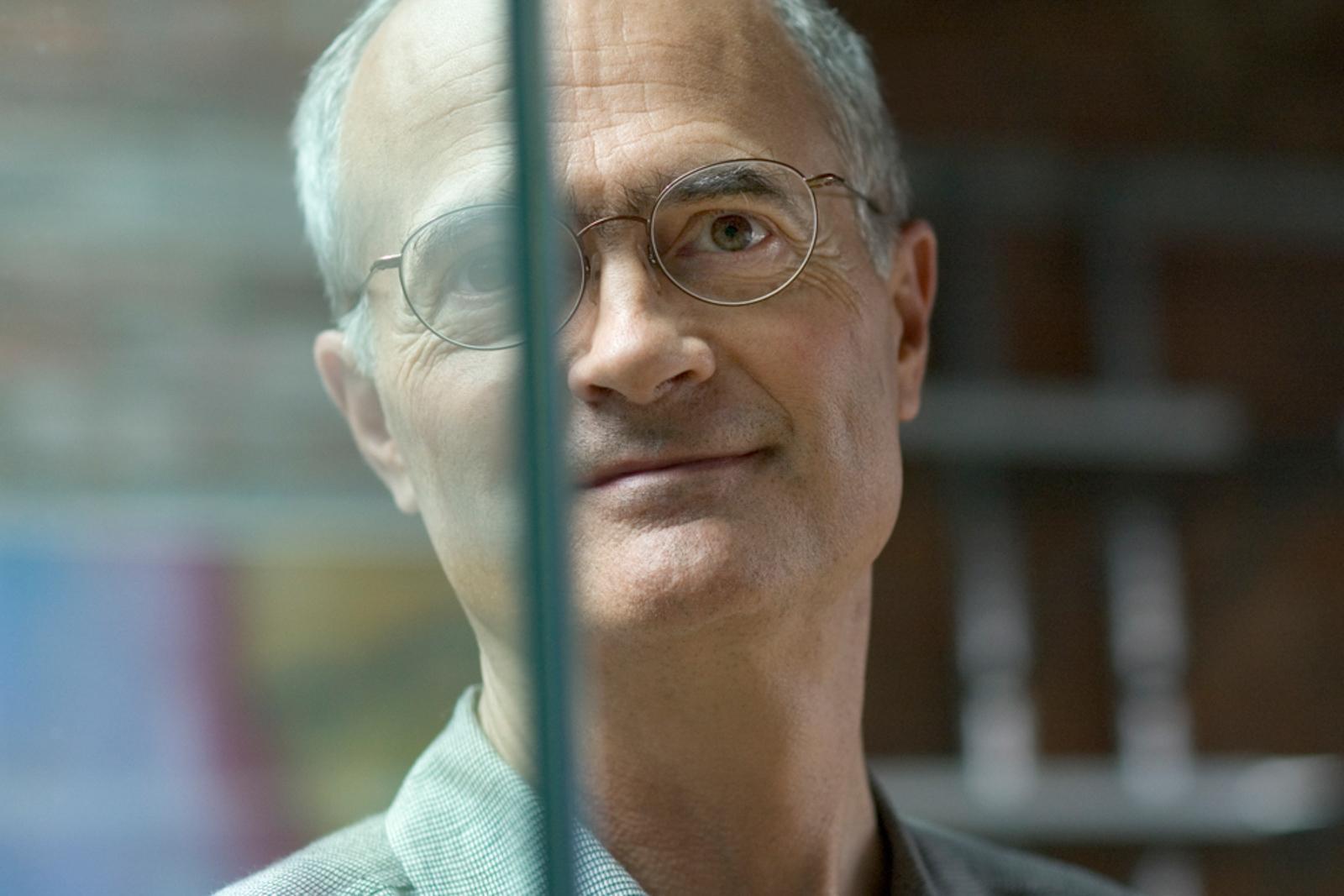 Portrait of older man looking pensive, seen through glass