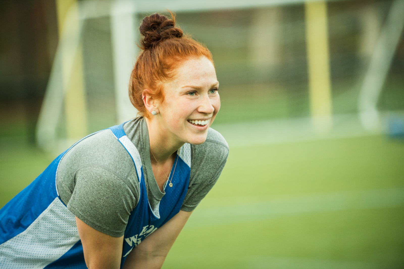 Student playing sports outdoors, smiling