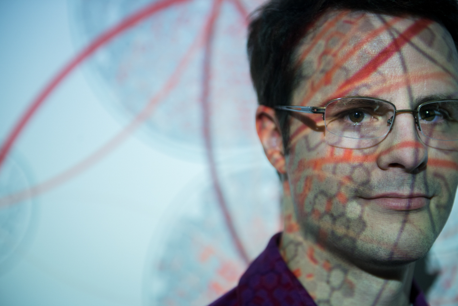 Close up of man wearing glasses with pattern projected over his face