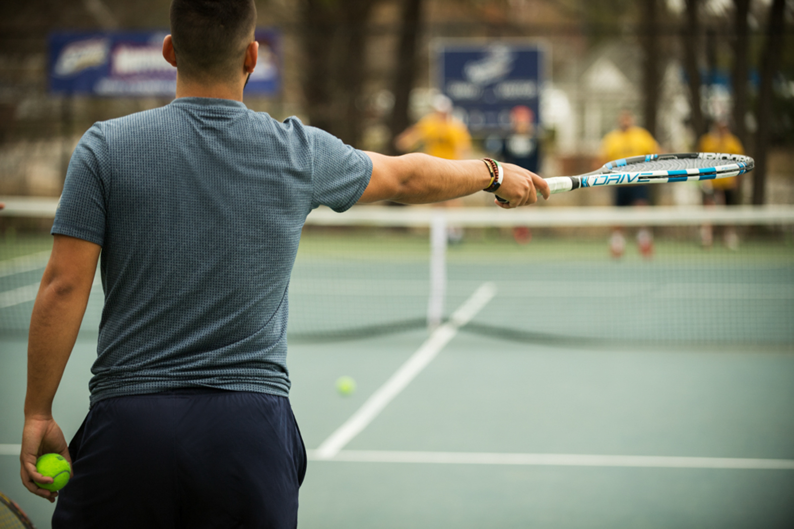 Student playing tennis outdoors, seen from behind
