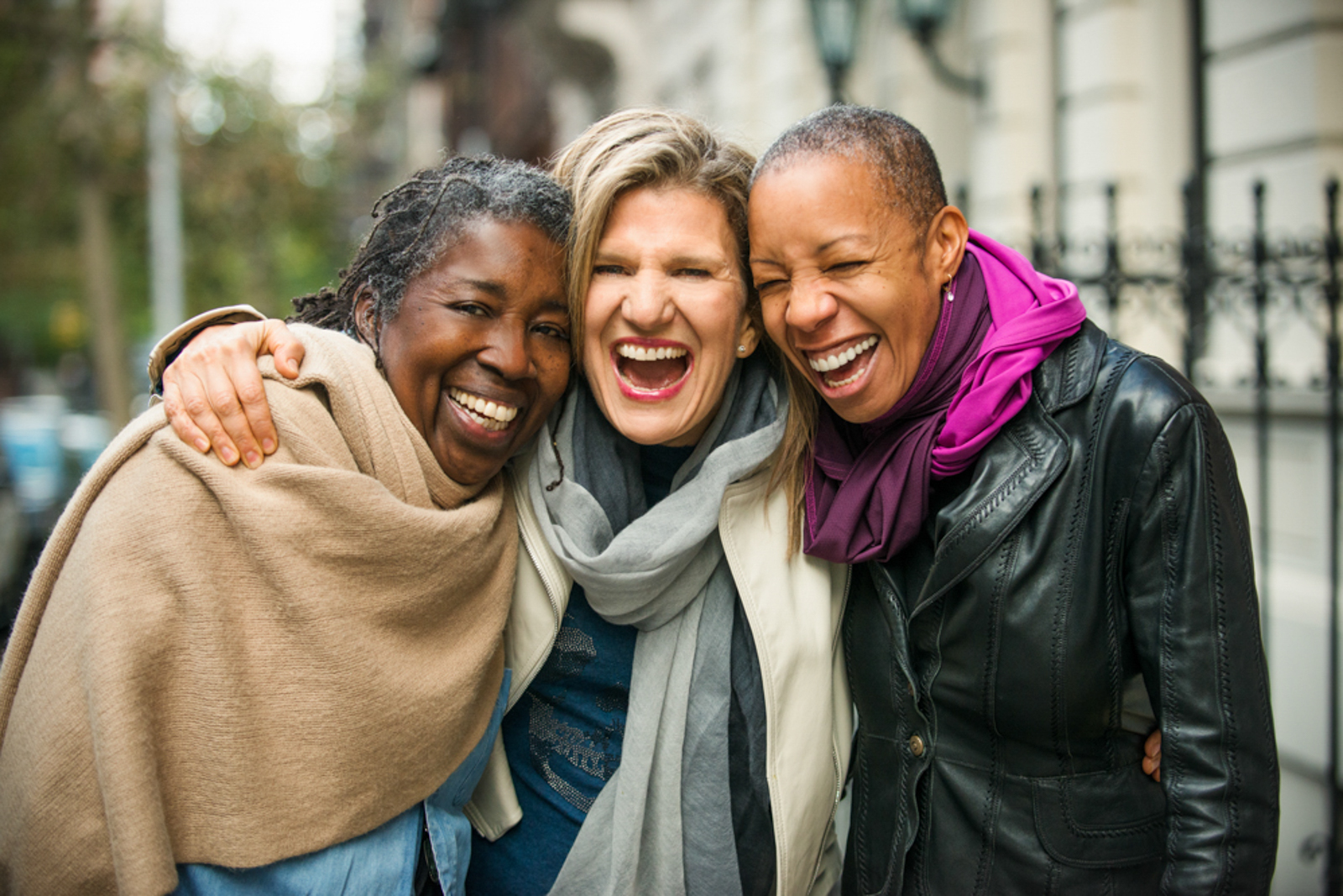 Three women hugging and smiling in a New York City street