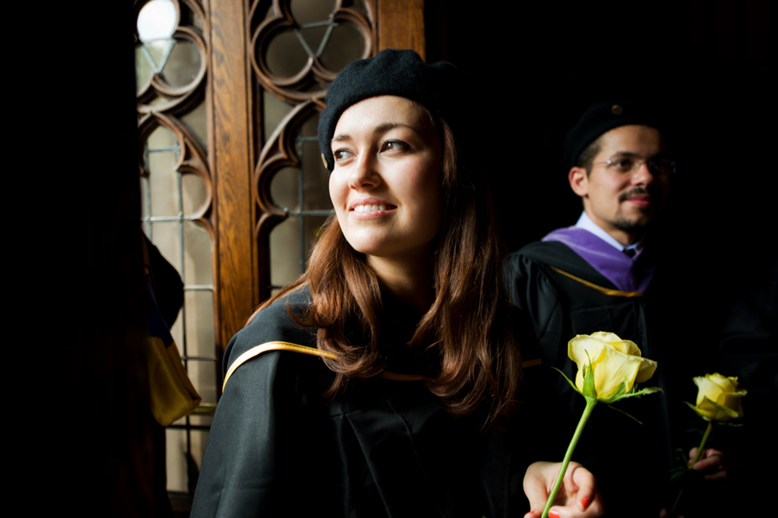 Graduating students in dim lit room, female student in foreground holding flower, smiling