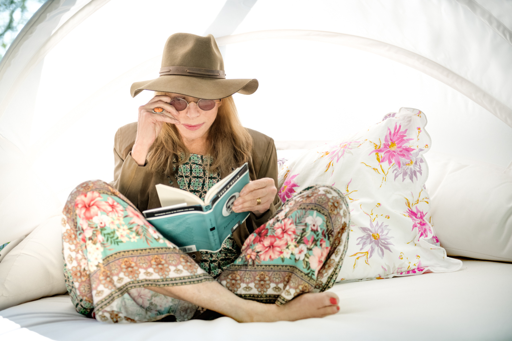 Portrait of musician Carly Simon sitting in bed with a book