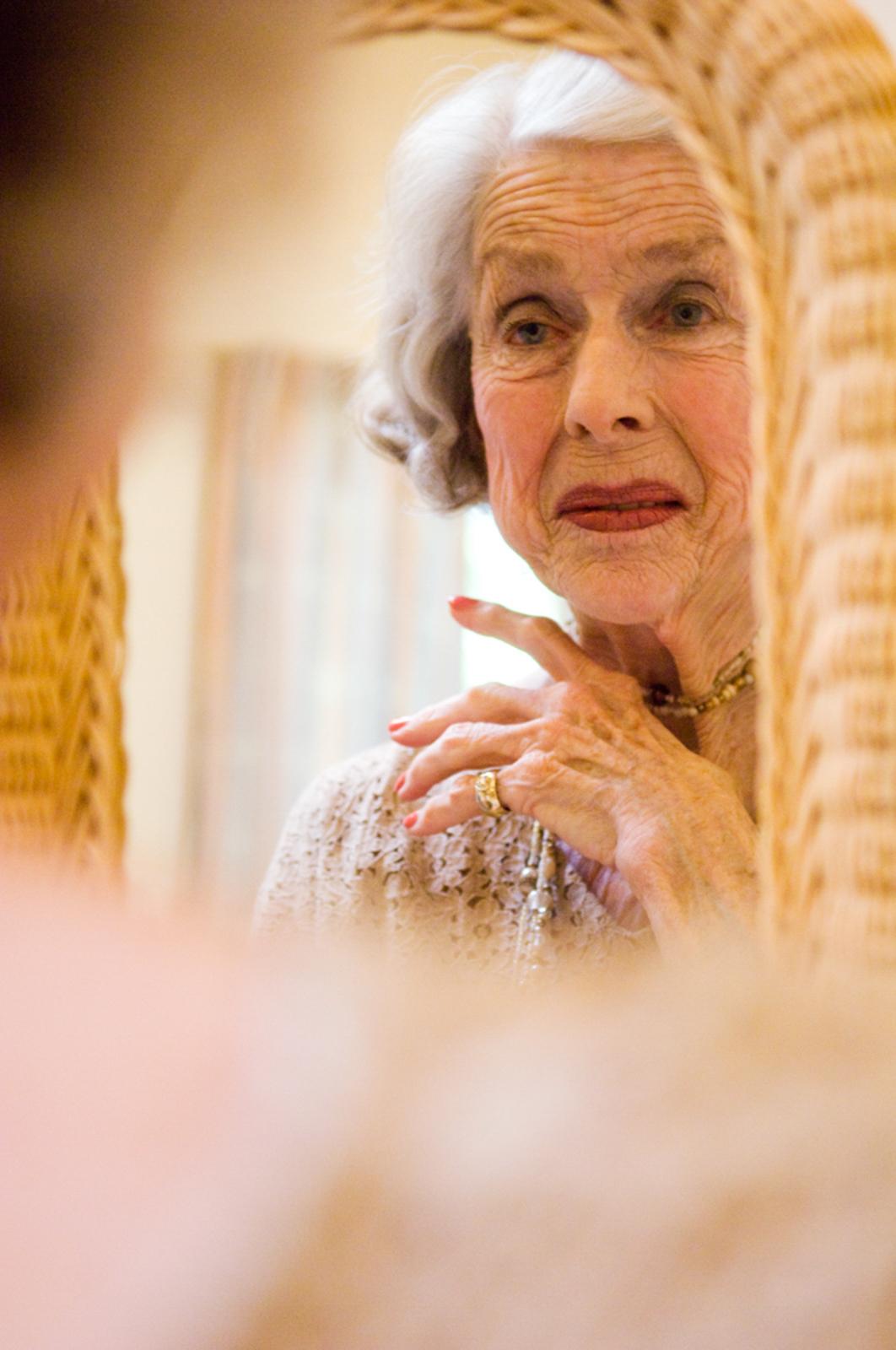 Portrait of elegant elderly woman staring at the mirror