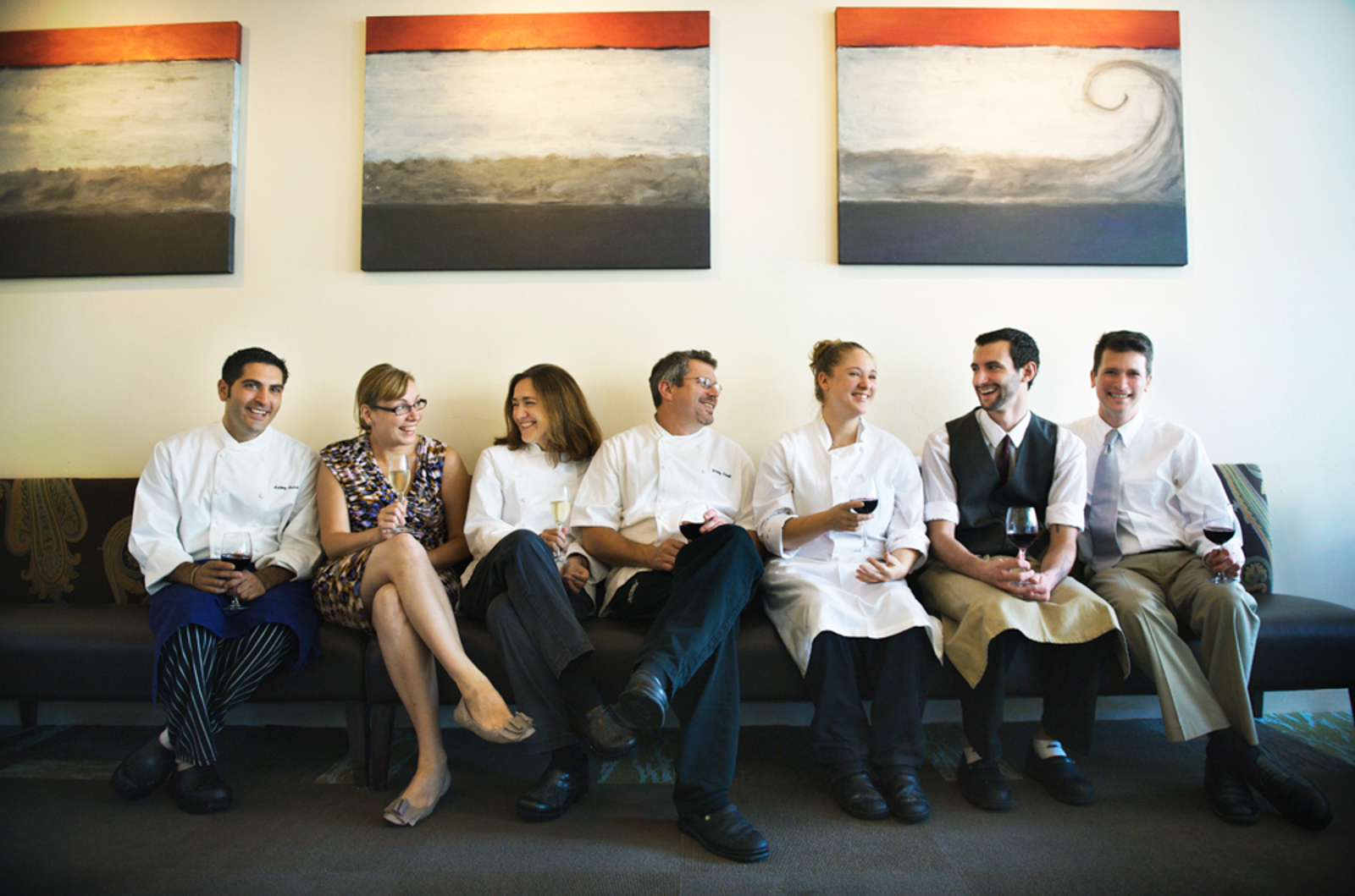 Group of chefs sitting in a couch smiling, with artwork