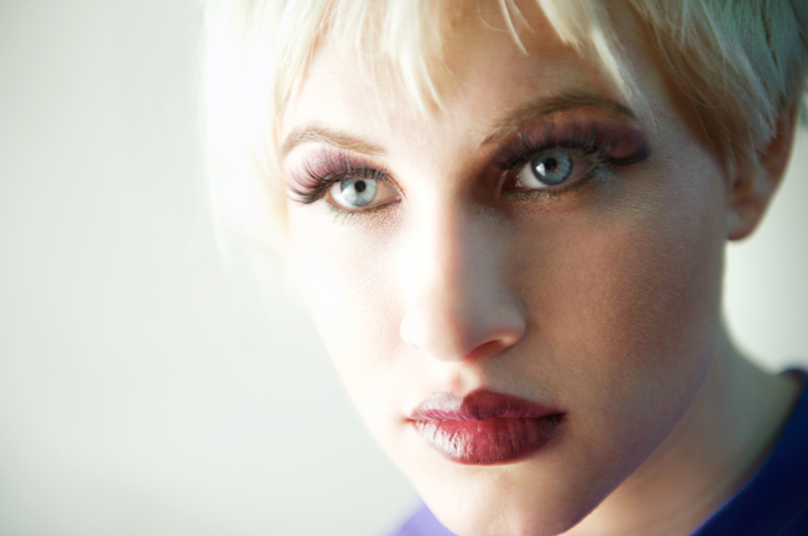 Portrait of green eyed woman, with dramatic red lipstick, looking intense